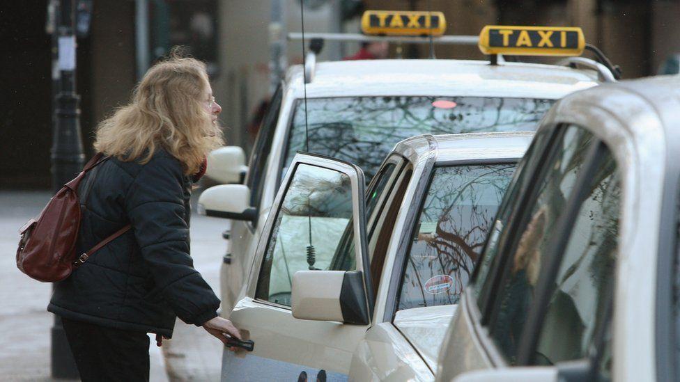 A woman prepares to climb into a taxi