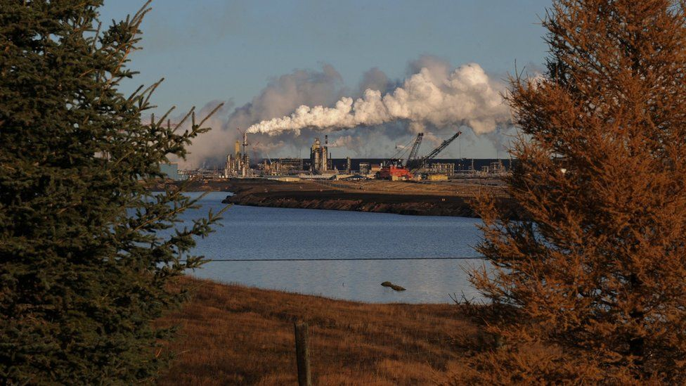 The Syncrude oil sands extraction facility behind a lake reclaimed from an old mine near the town of Fort McMurray in Alberta Province, Canada on October 22, 2009.