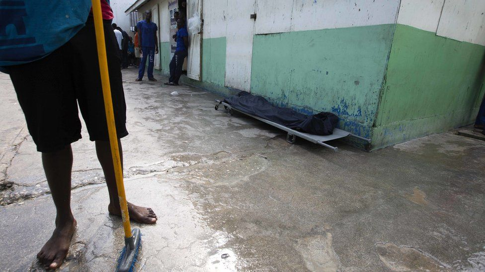 A prisoner stands near the body of an inmate, covered with a plastic tarp, who died of malnutrition inside the National Penitentiary in downtown Port-au-Prince