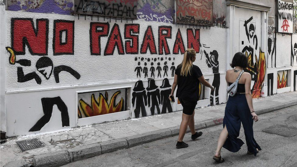 "Women walk past the slogan ""They shall not pass"", which has been spray-painted across various walls in Exarchia."