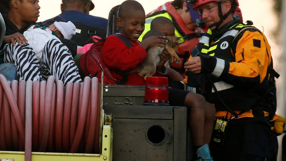 A member of FEMA hands a child his dog on a truck as people are evacuated from a flood area as a result of Hurricane Mathew in Lumberton, North Carolina, U.S. October 10, 2016