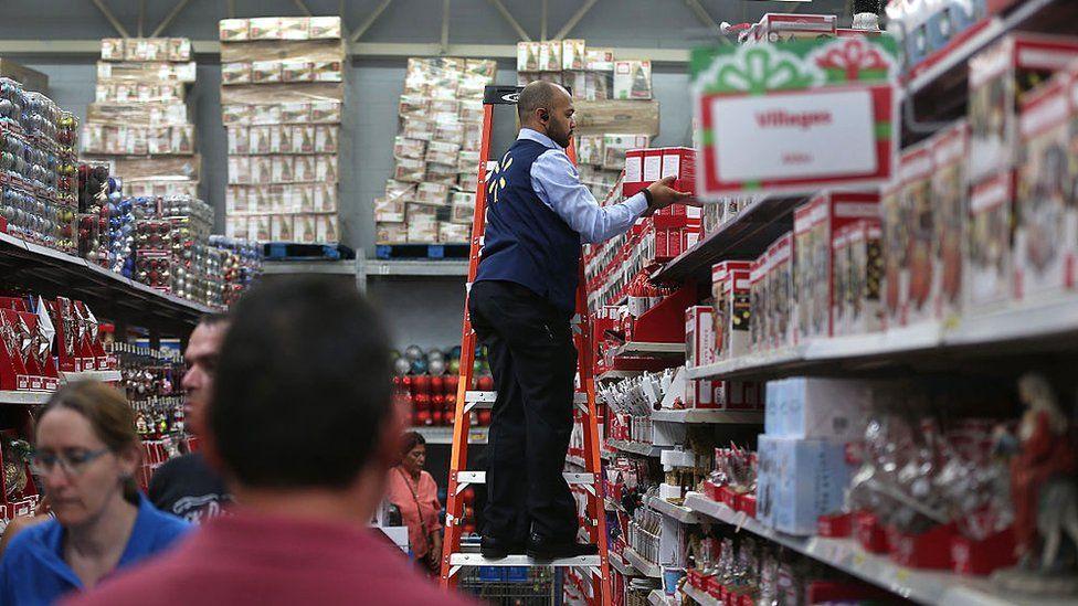 A Walmart employee stocks a Christmas shelf