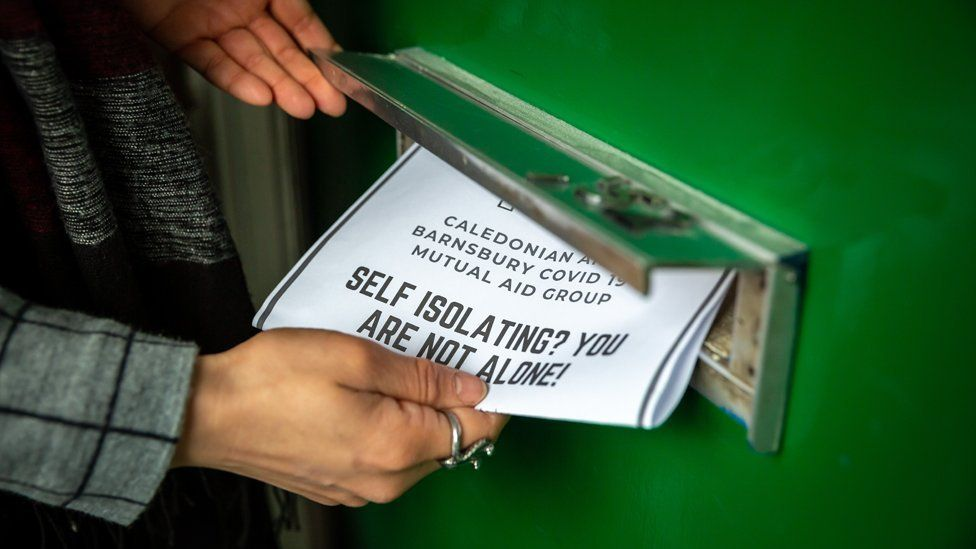 """A leaflet being pushed into a letterbox reads """"self-isolating - you are not alone"""""""