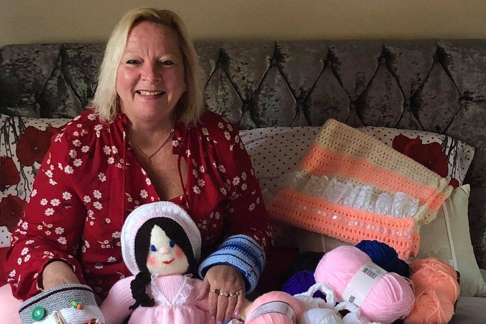 Susan Crossland surrounded by knitted items