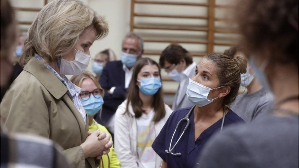 Belgium's Queen Mathilde (left) visits a crisis centre after flooding, July 2021