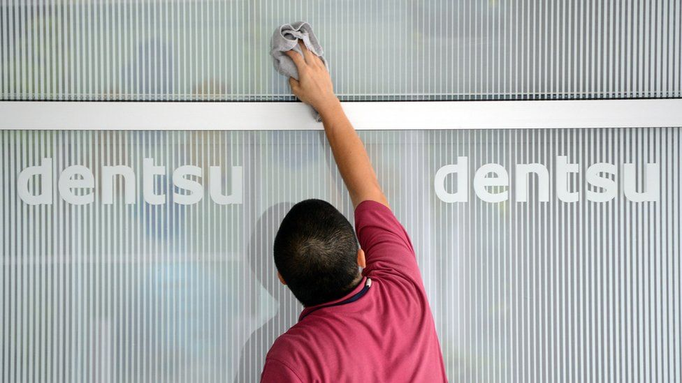 This picture taken on July 14, 2012, shows a man cleaning a window at an entrance of the headquarters of Japan's top advertising agency Dentsu