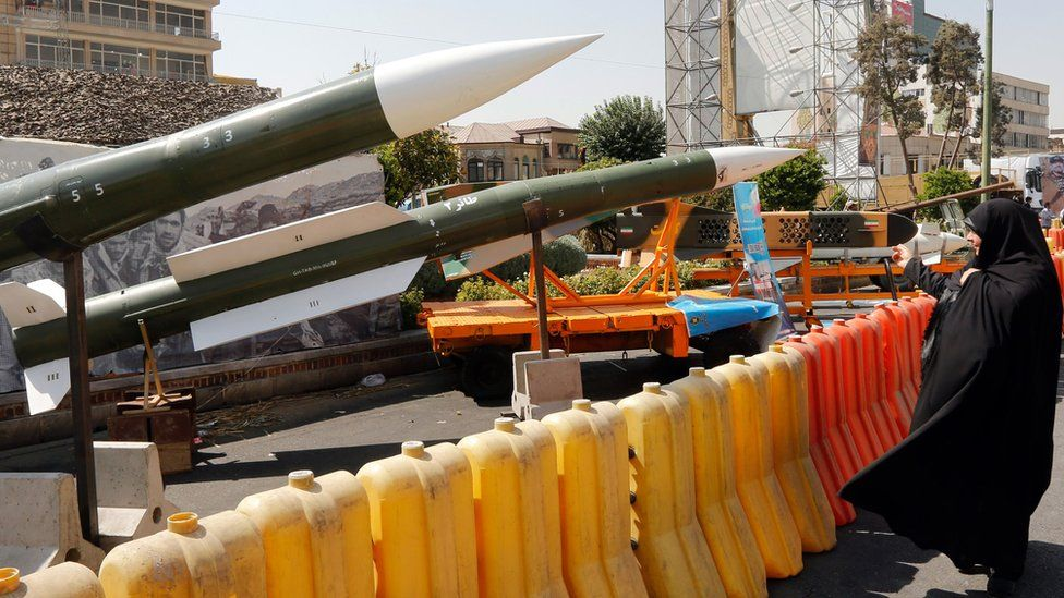A woman looks at missiles on display during a street exhibition in Tehran, Iran