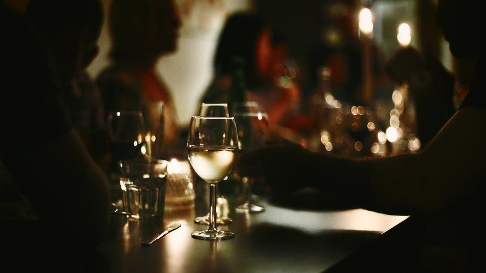 People dining in dimly lit room