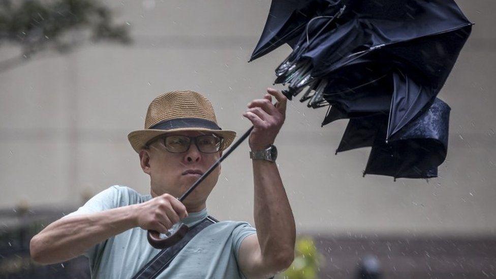 Man struggles with umbrella in Shanghai