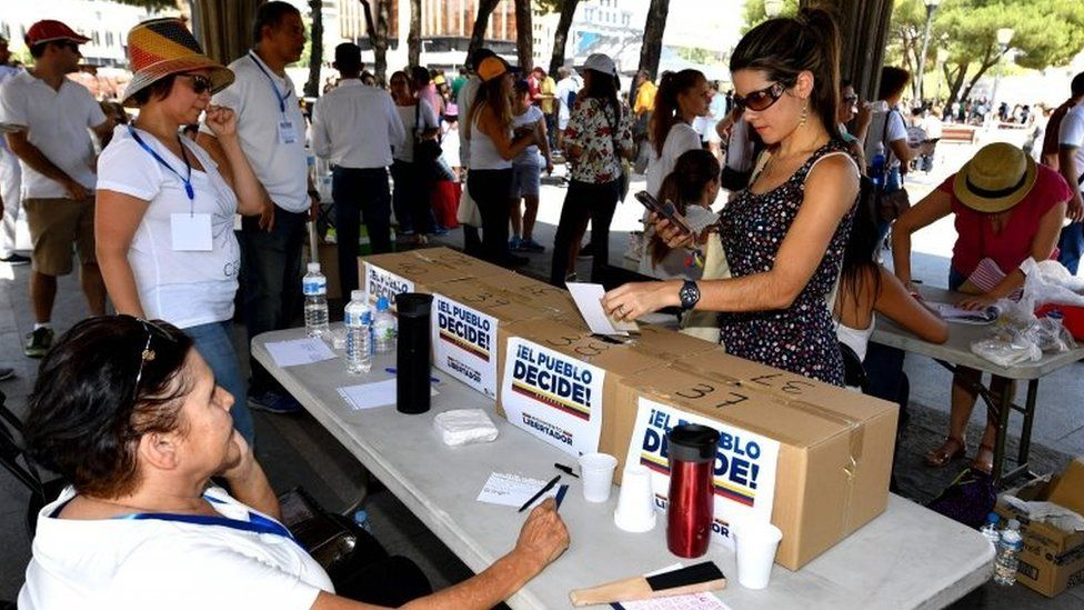 """A Venezuelan resident in Madrid votes at a polling station during a symbolic plebiscite on president Maduro""""s project of a future constituent assembly, called by the Venezuelan opposition and held at the Plaza Colon in Madrid on July 16, 2017"""
