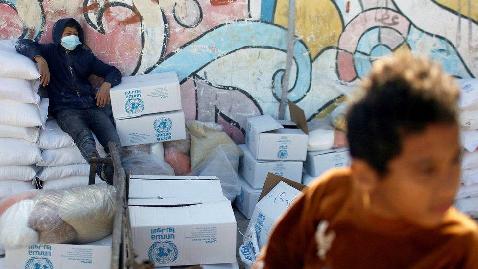 A Palestinian boy sits on a bag of flour at an aid distribution centre run by the United Nations Relief and Works Agency in Gaza City