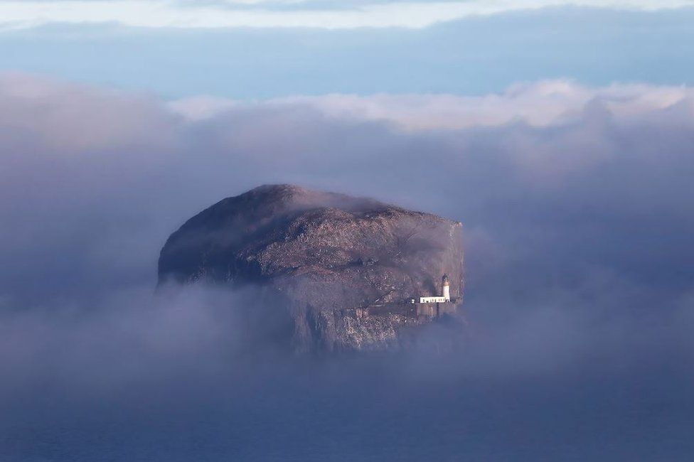 Bass rock surrounded by sea fog
