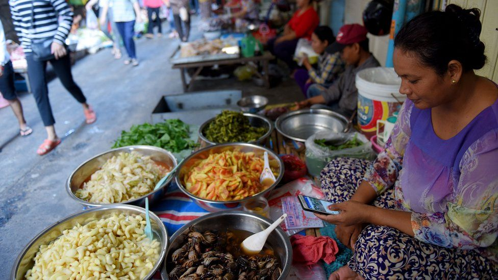 Woman on a smartphone at a market in Cambodia