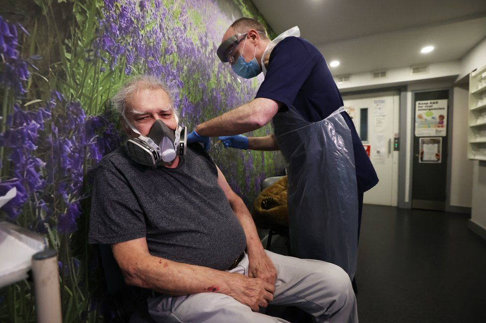 Eighty-four-year-old John Grey receives a Covid-19 vaccine