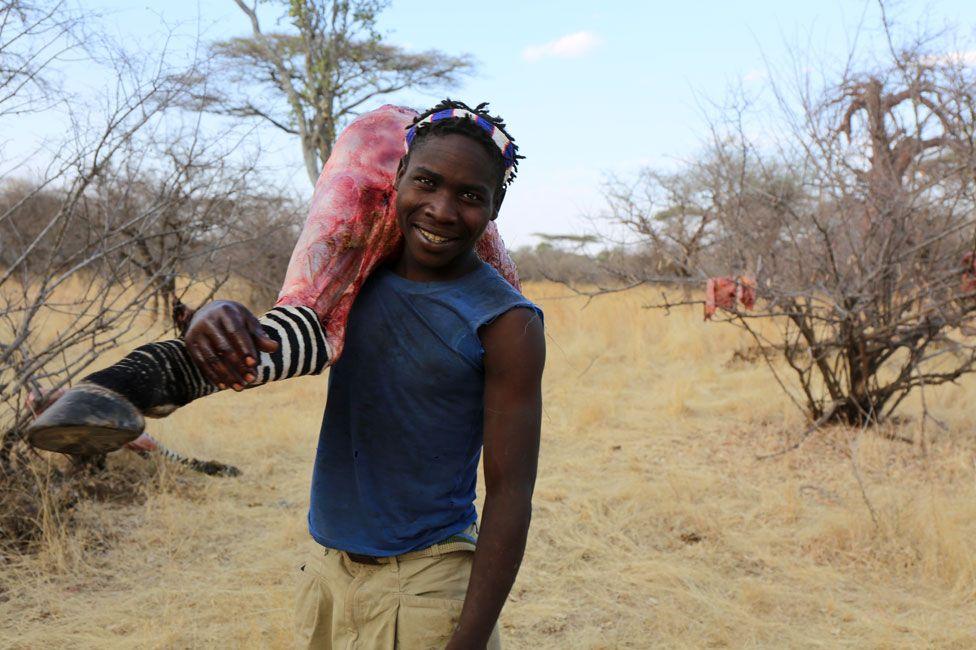 Hadza carrega a perna de uma zebra