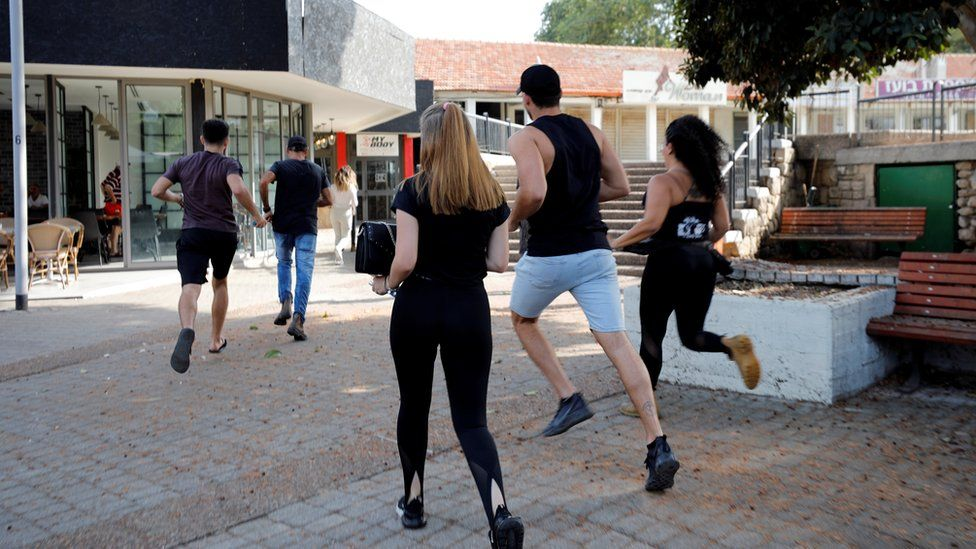 People run to take shelter when an air raid siren sounds in Ashkelon, southern Israel (13 November 2019)