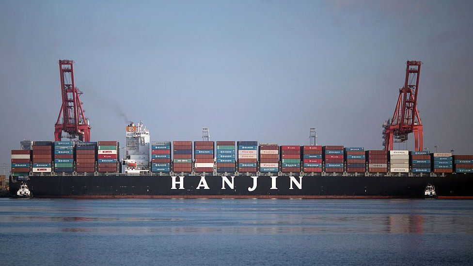 Tug boats push the Hanjin Greece container ship to dock for unloading at the Port of Long Beach, California