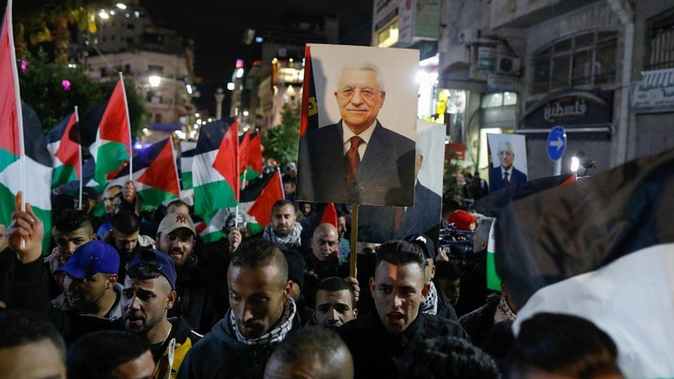 Palestinian protesters wave the national flag and a portrait of president Mahmud Abbas during a demonstration in the West Bank city of Ramallah on January 28, 2020