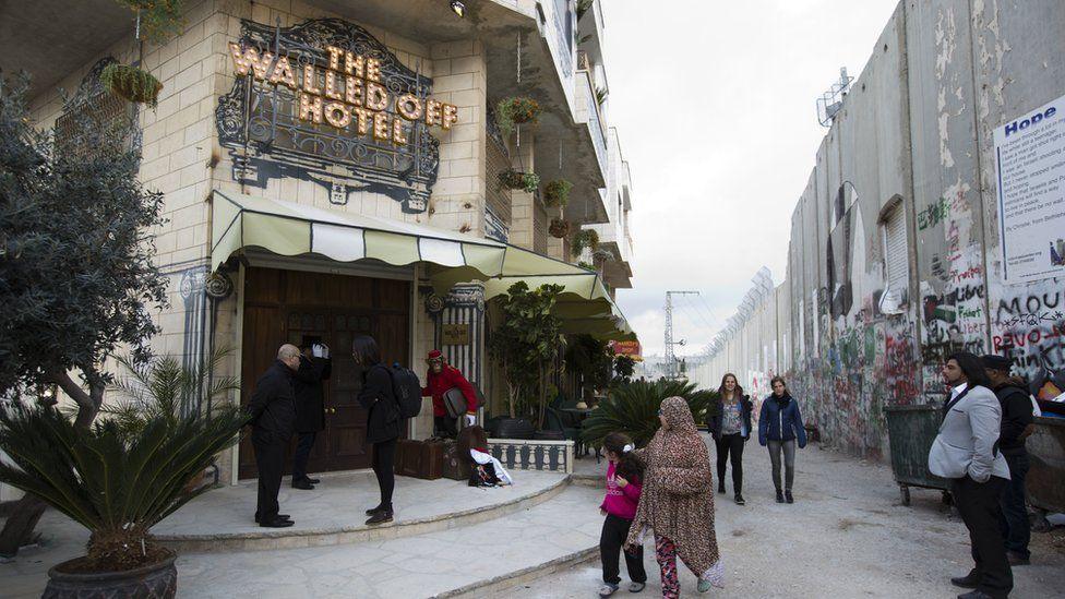 "People pass by the ""The Walled Off Hotel"" and the Israeli security barrier in the West Bank city of Bethlehem, Friday, March 3, 2017."