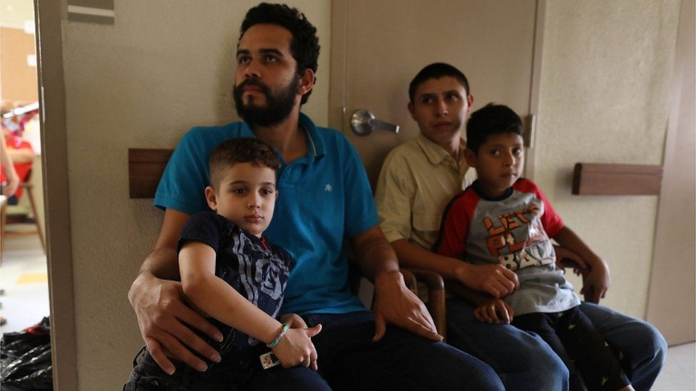 Migrant fathers and their sons sit in a facility after being reunited