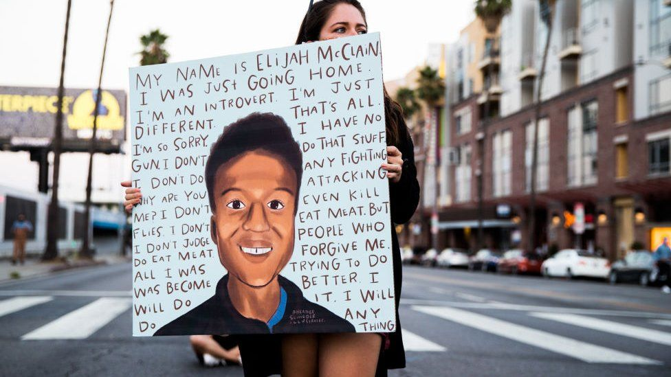 A person holds a sign at a candlelight vigil to demand justice for Elijah McClain on the one year anniversary of his death