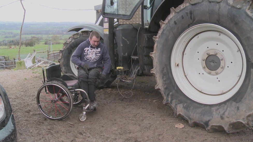 Matthew Evans transfers from his wheelchair to the tractor using a specially built hoist