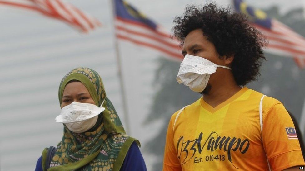 Two people wear masks amid haze in Malaysia