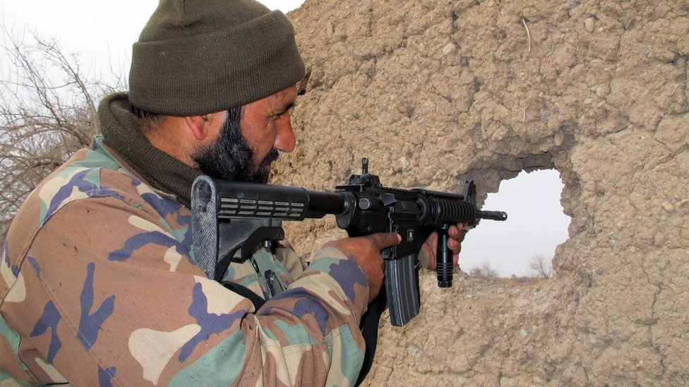A member of the Afghan security forces takes up a position during an operation against Taliban fighters in Nad Ali district of Helmand province, Afghanistan, 26 December 2015