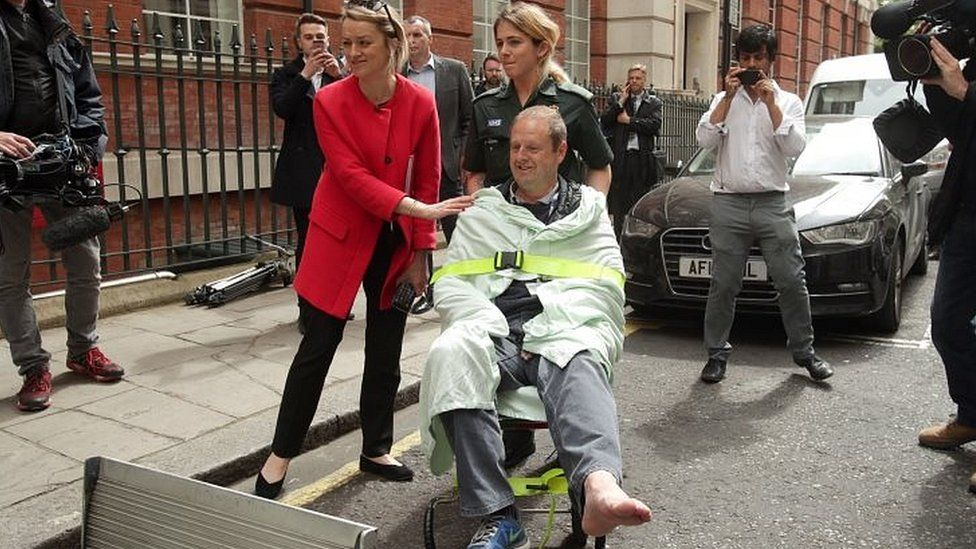 "BBC""s Laura Kuenssberg comforts her her colleague, BBC cameraman Giles Wooltorton, after the car carrying Jeremy Corbyn ran over his foot as it arrived at the Institute of Engineering in London"