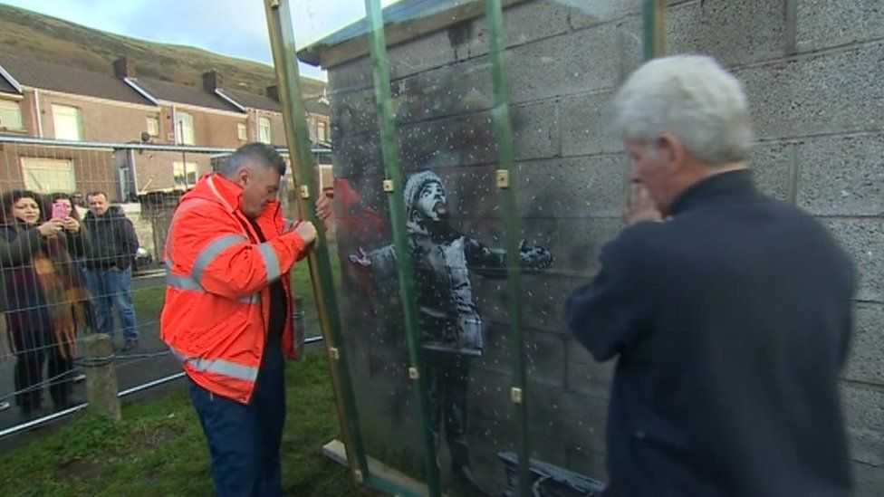 Plastic sheet being placed over the Banksy artwork in Port Talbot