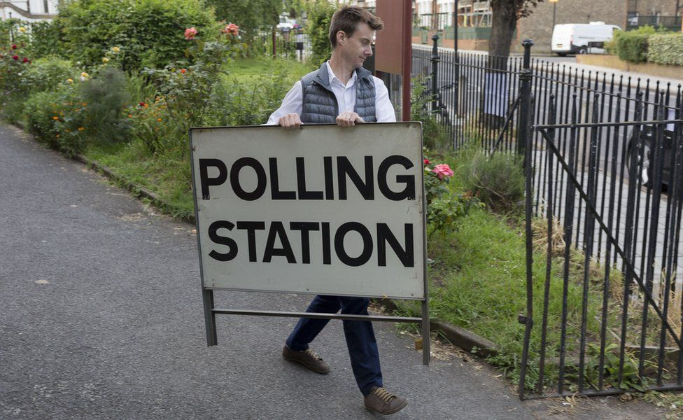 Man carrying a polling station sign
