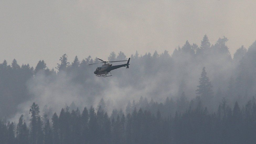A helicopter flies over a wildfire south west of the town of Cache Creek, British Columbia, Canada July 18, 2017