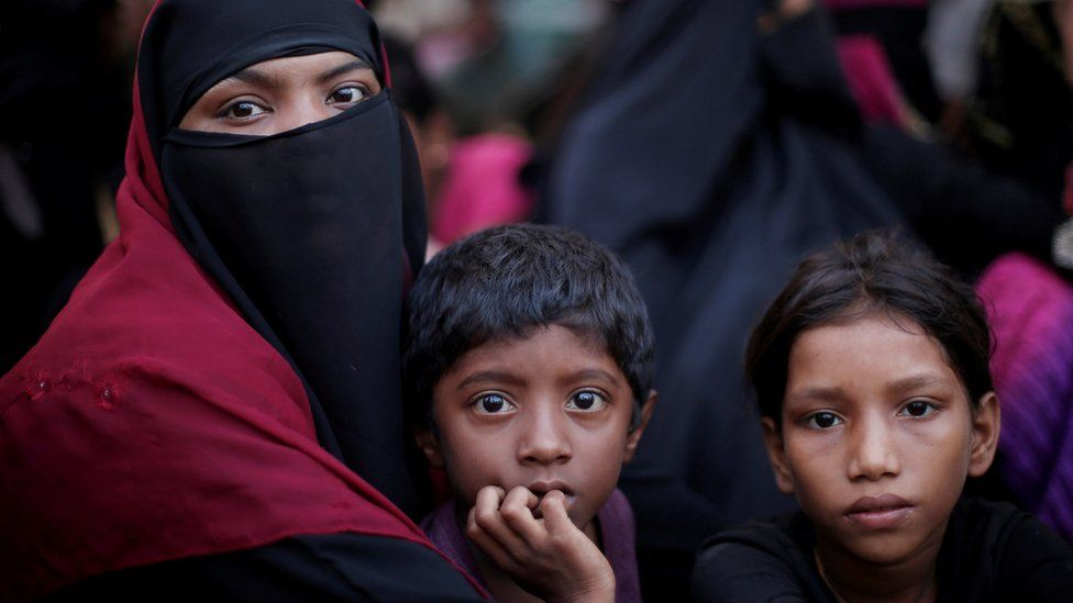A Rohingya refugee family sits in a queue as they wait to receive humanitarian aid at Kutupalong refugee camp near Cox's Bazar