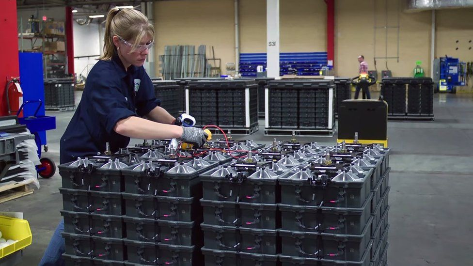 Woman working on stack of Aquion batteries