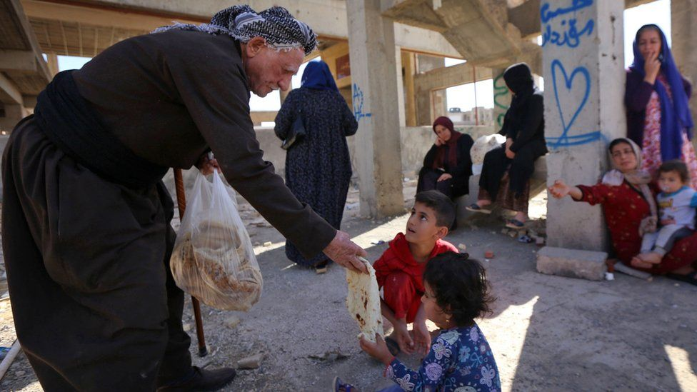 An Kurdish man distributes bread to a family of displaced people from Kirkuk province at a building site in Irbil, Iraq (19 October 2017)