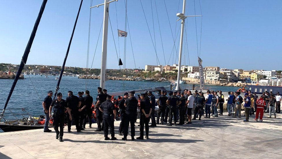"Italian law enforcement officers stand on the pier as the Italian NGO Mediterranea Saving Humans"" Alex migrant rescue ship carrying 41 migrants rescued off Libya Thursday arrives in the port of Lampedusa,"