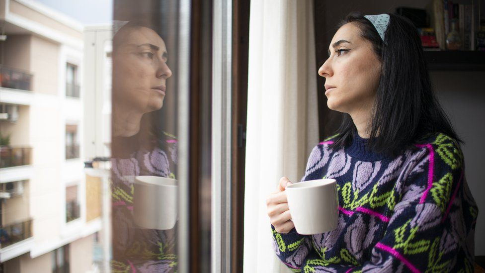 Woman looking out of window (file image)