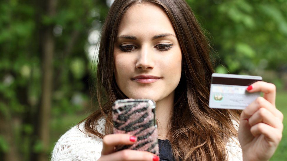 Young woman with smartphone and payment card