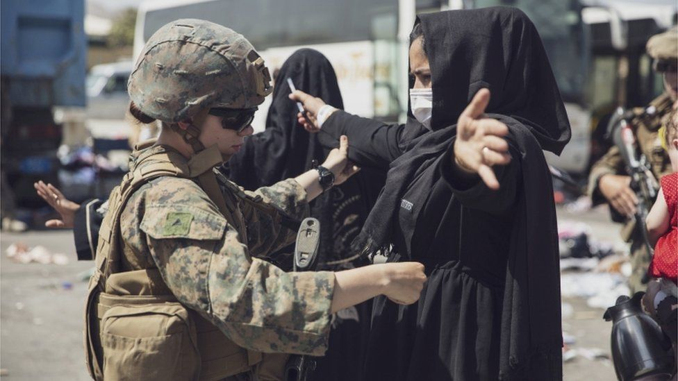 A U.S. Marine checks a woman as she goes through the Evacuation Control Center (ECC) during an evacuation at Hamid Karzai International Airport