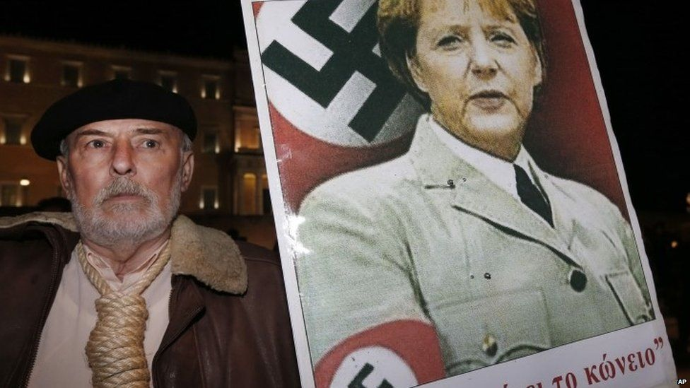 A man holds a poster with a picture of German Chancellor Angela Merkel wearing a swastika (November 2012)