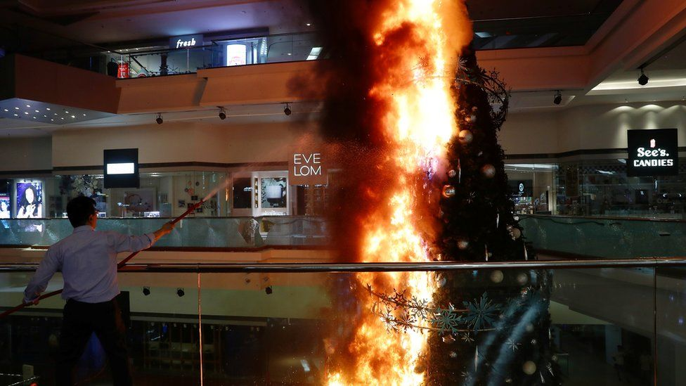 A Christmas tree inside a shopping mall on fire