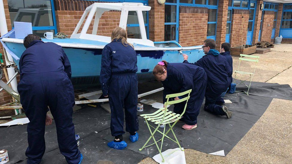 Youngsters renovating the boat before the fire