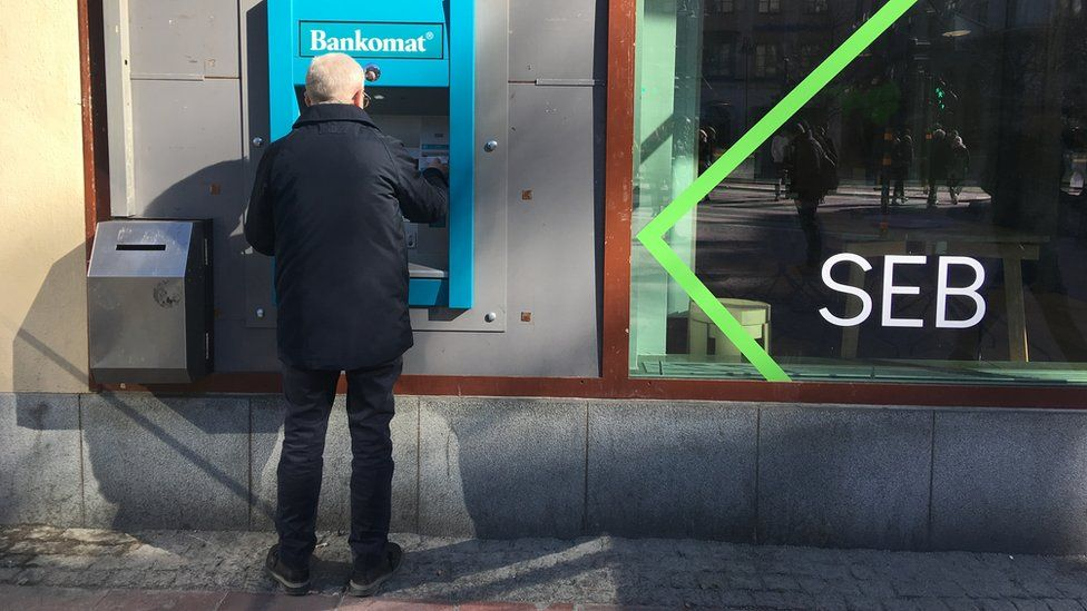 Old person using a cash machine