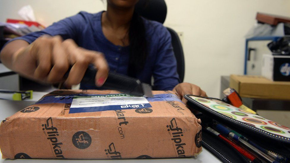 An Indian woman opens a parcel in her office after ordering it from an online shopping website in Mumbai in 2013.