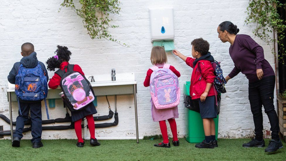 Pupils wash their hands as they arrive on the first day back to school at The Charles Dickens Primary School on September 1st 2020