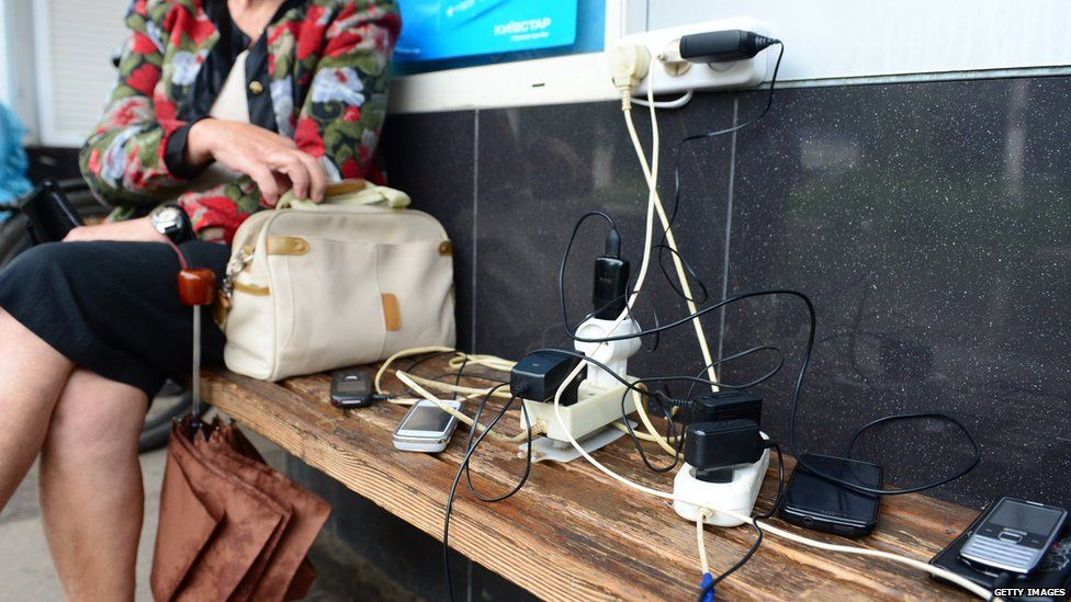 Residents wait as they charge their mobile phones at a kiosk with a rare working power outlet in the besieged city of Slavyansk on June 25, 2014