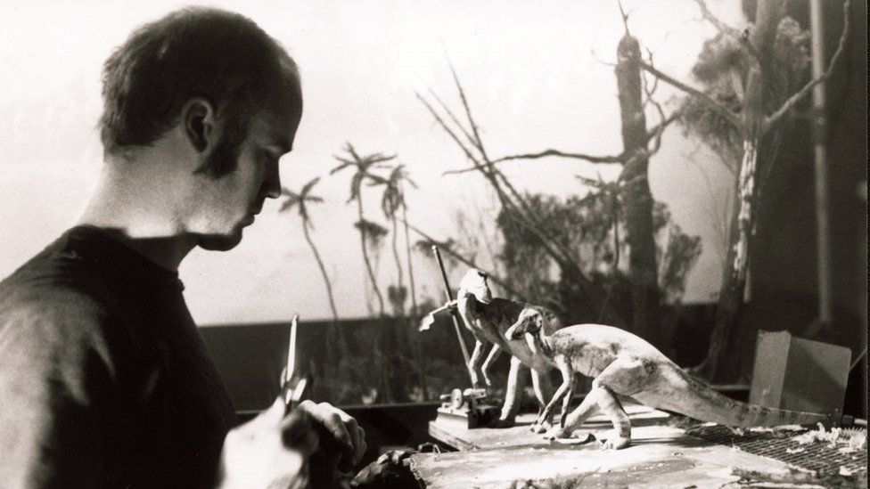 Black and white photo of a man working on dinosaur models