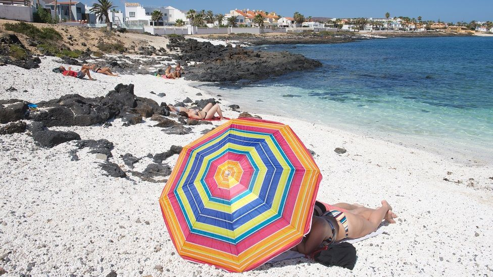 People enjoy a warm day at the beach of Corralejo, Fuerteventura, Canary Islands