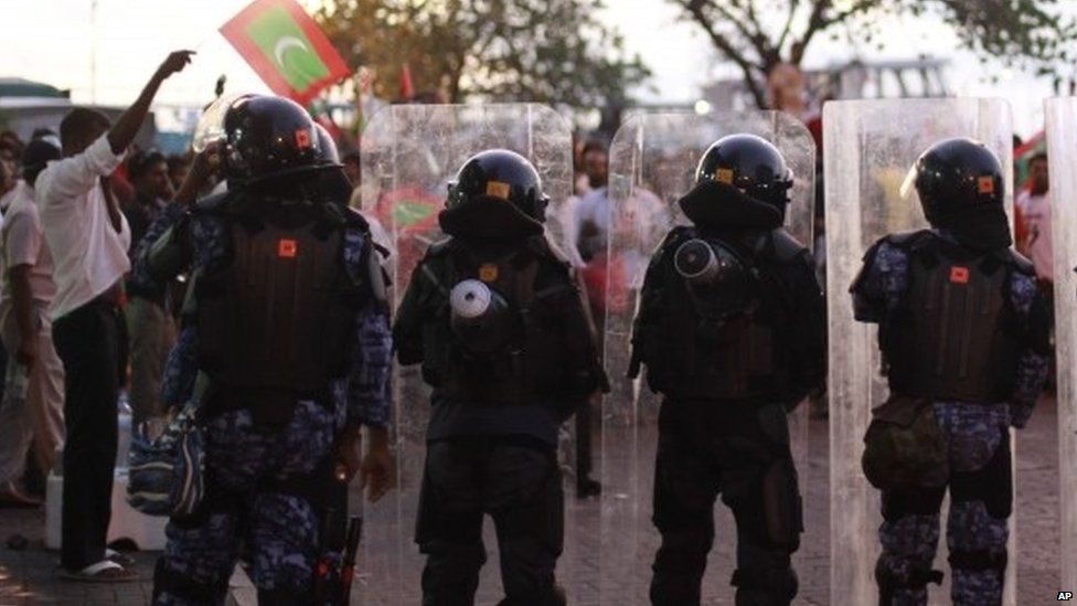 Policemen face opposition supporters during a protest to demand the resignation of Maldives President Yameen Abdul Gayoom (01 May 2015)