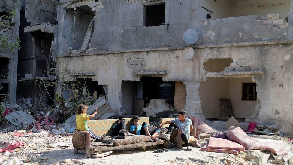 Palestinian children sit near the rubble of houses in Gaza that were destroyed in Israeli air strikes (9 June 2021)